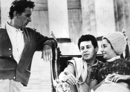 "Elizabeth Taylor on the lap of Eddie Fisher, her husband at the time, on the set of ""Cleopatra"" in Rome in early 1962. Richard Burton, her husband to be, would pry her away from Fisher before the end of the year."