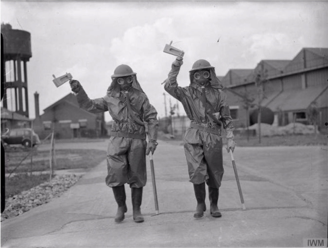Two airmen wield gas rattles during an exercise during World War II. Imperial War Museum.