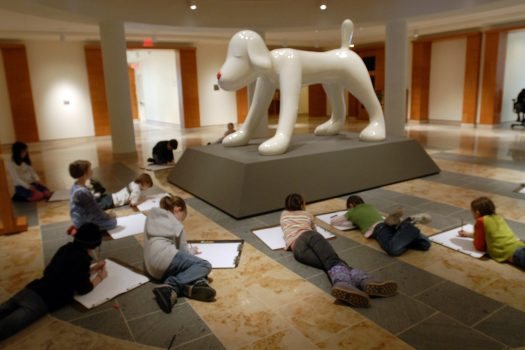 A group of young kids lie down and draw a large dog statue/