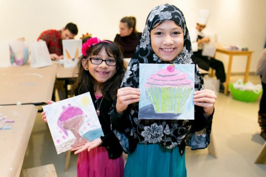 Two kids hold hand-drawn pictures of a cupcake and ice cream at Family Day