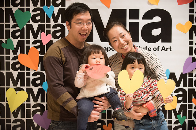 Two adults, each holding small children who are holding paper cut-outs of hearts in front of a backdrop of Mia logos.