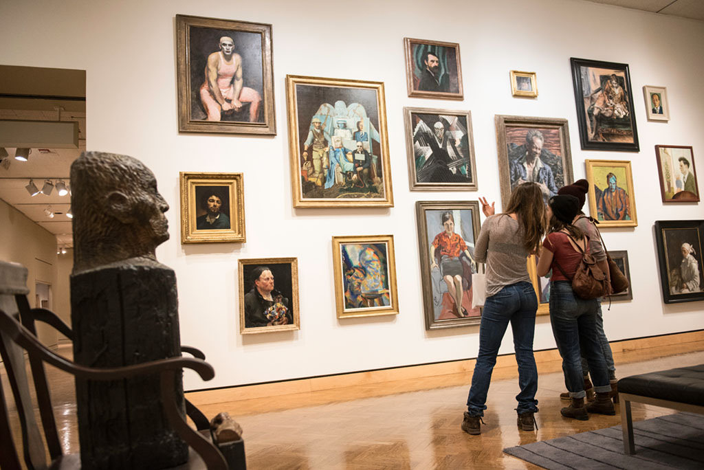 Two visitors looking at painted portraits that are hung in floor to ceiling in gallery.
