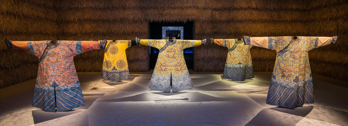 Six standing Chinese robes with spread arms displayed in gallery.