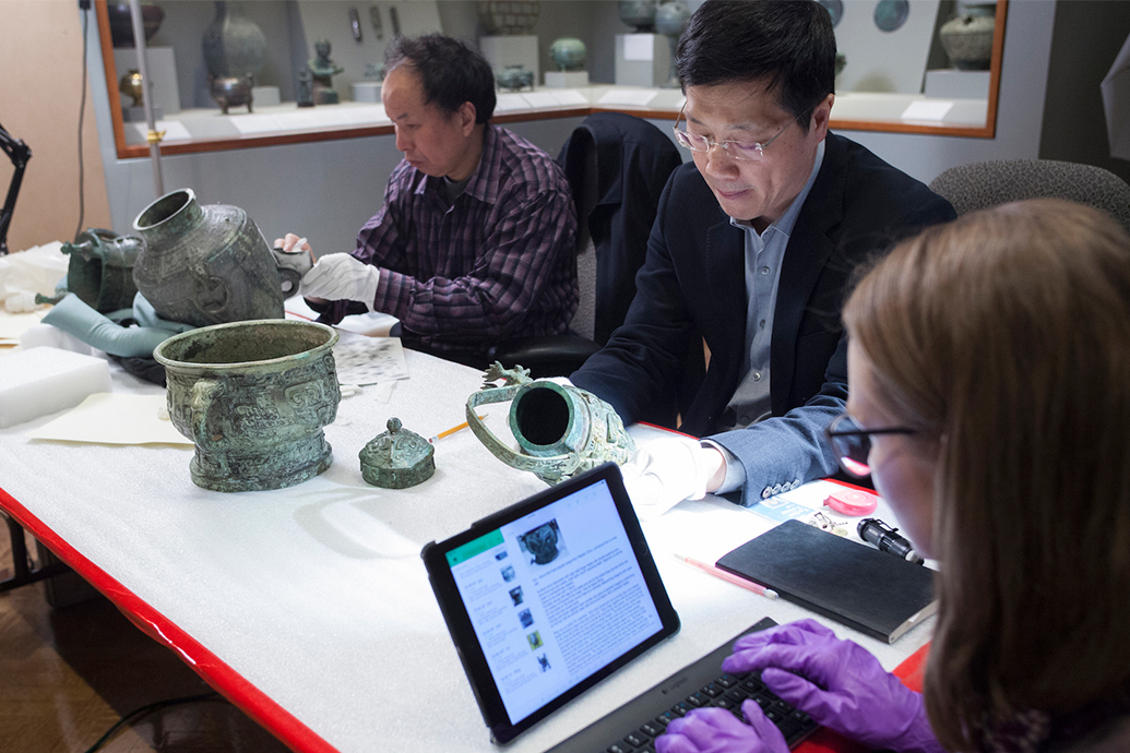 Three people examining and cataloging bronze objects.