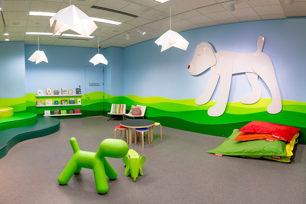 Mia's family center with pillows, a small table and stools, and a large cutout of a dog on a wall.