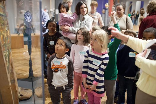 A group of kids listening to a speaker, and looking at an object in vitrine.