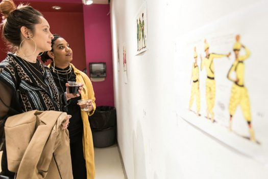 Two visitors looking at drawings pinned on wall.