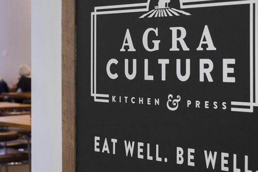 The Agra Culture restaurant sign with white letters over a black background.