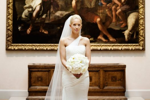 A bride holding white flowers standing in front of a large, baroque painting.