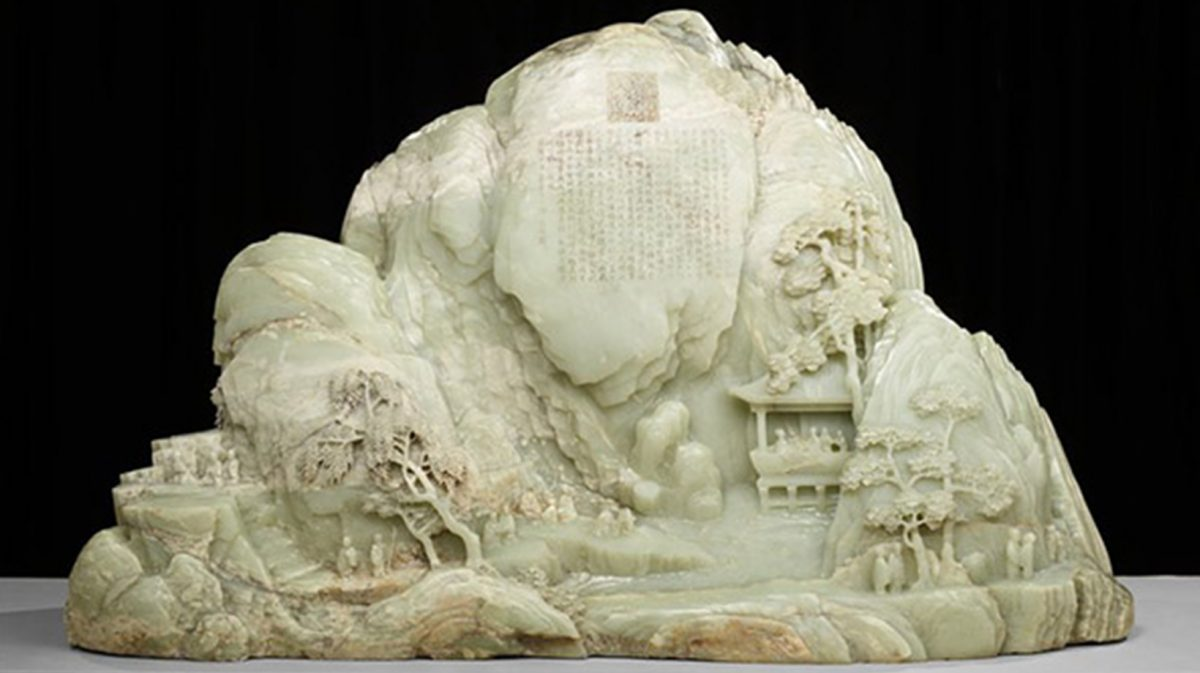 Jade carving of mountainous landscape that includes trees, people, and buildings.