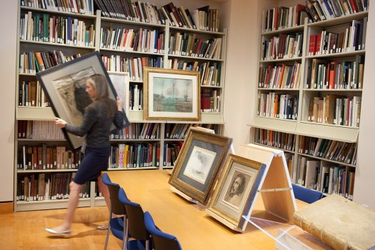 A woman carrying a framed picture in Mia's library.