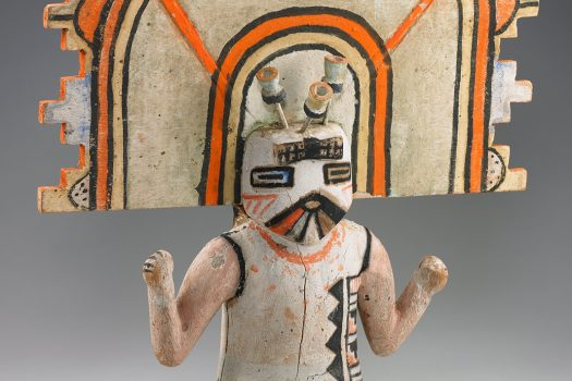 An orange and white figure of a Butterfly Maiden Kachina.