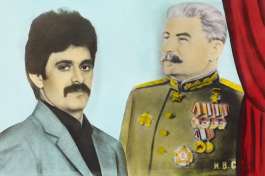 Aniline colored photograph of a man with dark hair and mustache wearing blue on the left, and Stalin wearing a green shirt with many medals on the right. Next to Stalin is a section of a red curtain.