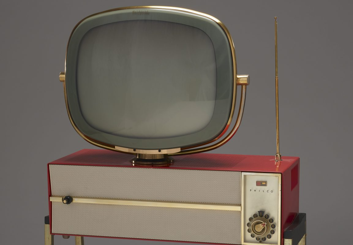 An antique gray and gold television with rounded corners and a red speaker.
