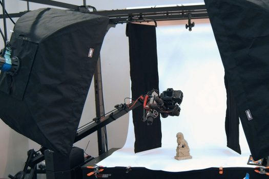 A lion staue sits on a white backdrop, while being photographed by a large robot.