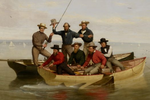 Seven men sit on two boats in the water. One holds a fishing pole.