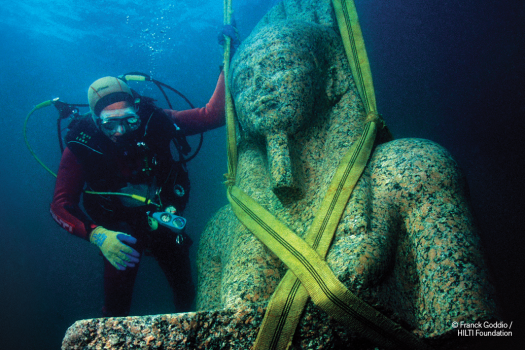 A scuba diver examines a massive Egyptian sculpture and readies it for excavation from under water.