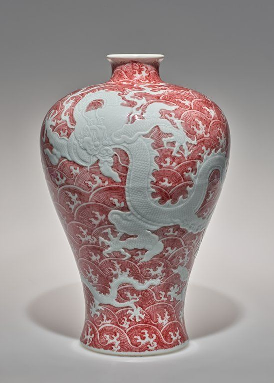 A ceramic vase with red circular designs overlain with a white dragon. The vase is wide at the top, and tapers down towards the bottom.