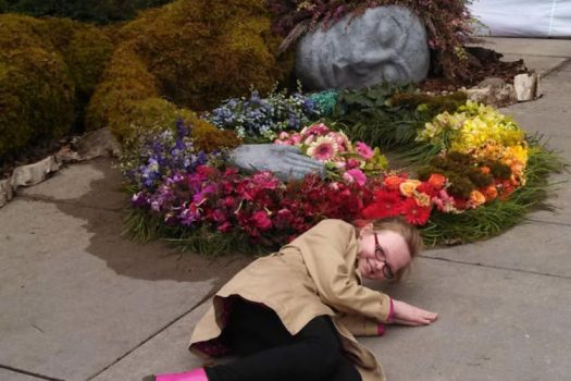 A girl lying on the ground in imitation of a moss, flower and stone sculpture.