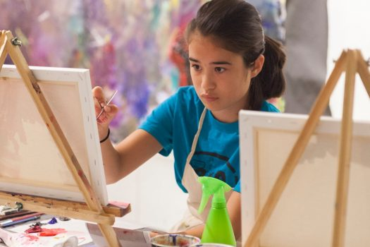 A girl painting a canvas.