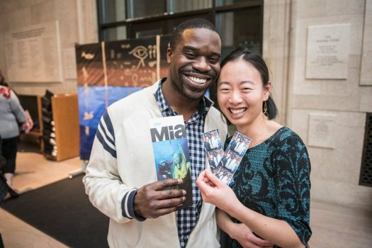 "Two visitors smiling with Mia's ""Egypt's Sunken Cities"" brochure and photos from photo booth."