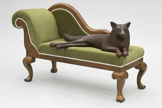 A pale green couch with an armrest only on the left side. A dog-like animal lies across the couch.