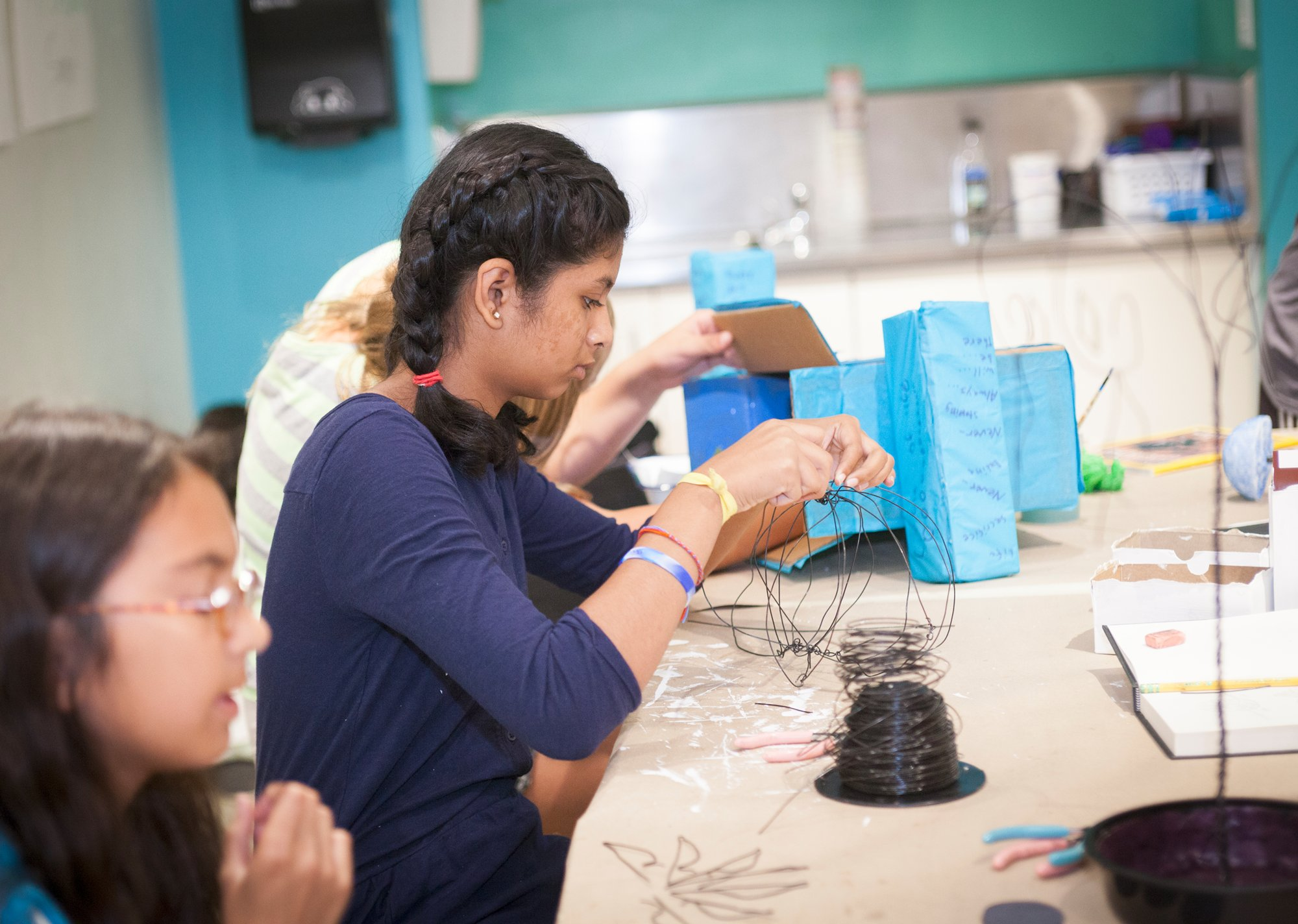 Two students in blue shirts sculpt with wire in Mia's studio classroom.
