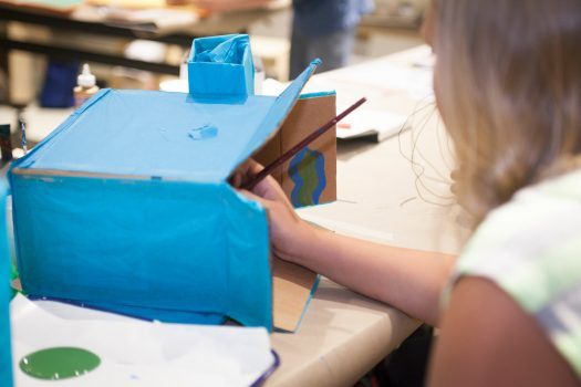 A student in a white shirt paints a cardboard box with blue paint in Mia's studio classroom.