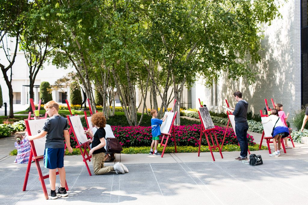 A group of kids draw on red easels in Mia's courtyard.