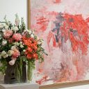 A vase filled with flowers sits on a pedestal next to a painting.