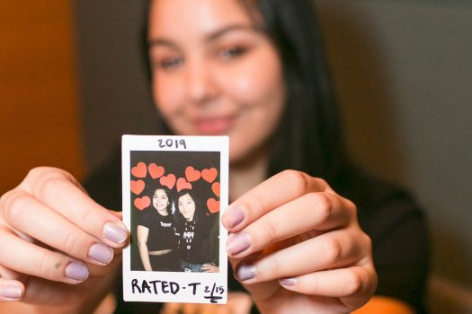 A teenage girl holds a polaroid picture of herself and a friend taken at a Rated T event.