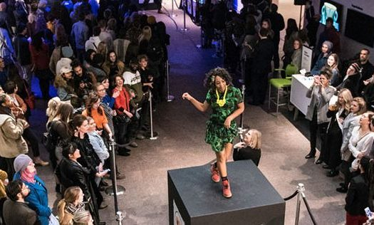 A woman models a green and black dress on a pedestal while a crowd watches.
