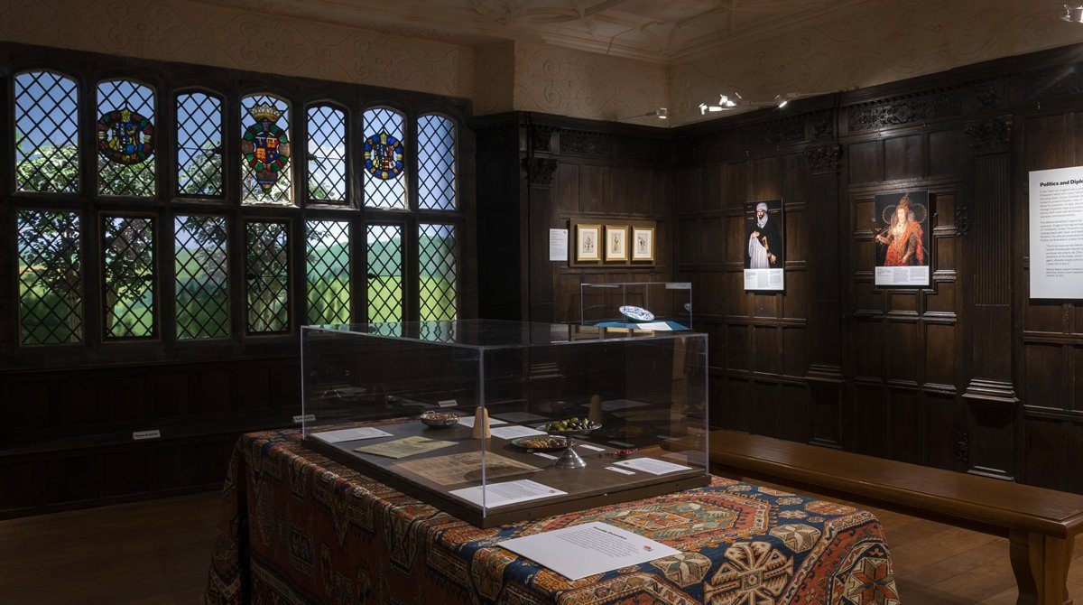 Room with dark wood paneled walls and large window featuring crests made out of stained glass. A Turkish rug covers a table in the center of the room and holds a museum case with objects inside.