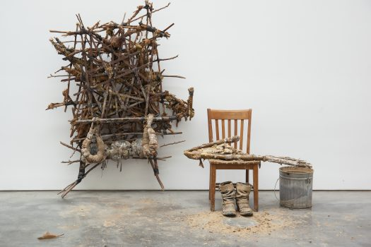 Kim Jones, Mudman Structure (large), 1974, sticks, mud, rope, foam rubber, shellac, and acrylic; shown with chair, boots, and bucket of mud, Courtesy of Zeno X Gallery, Antwerp. © Kim Jones, courtesy Gladstone Gallery, New York and Brussels & Zeno X Gallery, Antwerp.