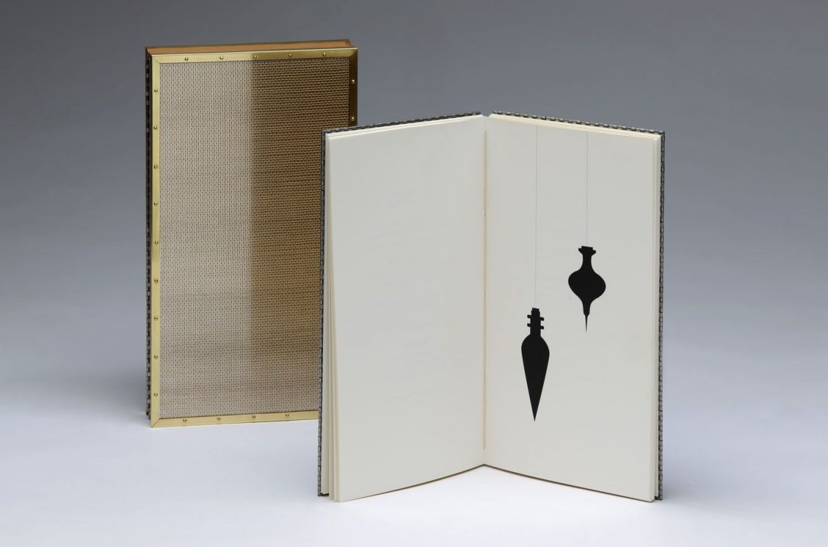 A gold bookcase next to an open book, on 1 page of the book there are 2 black ornaments.