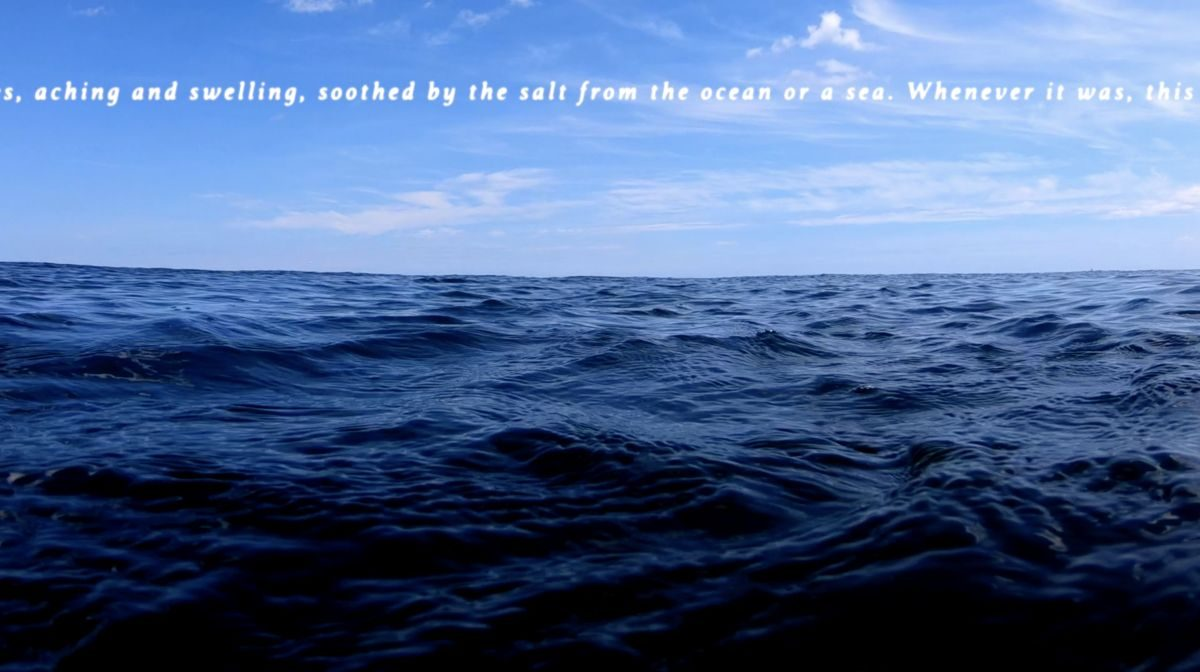 "A mass of blue water takes up the lower half of the screen while text is set against a blue sky with wispy clouds passing by. The visible text reads, ""aching and swelling, soothed by the salt from the ocean or sea. Whenever it was, this..."""