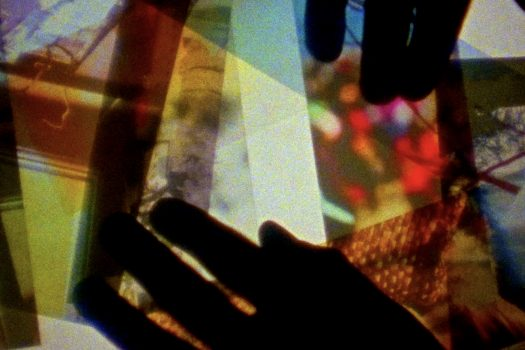 Colorful photos appear transparent against a white backlight. The silhouette of hands appears atop the photos.