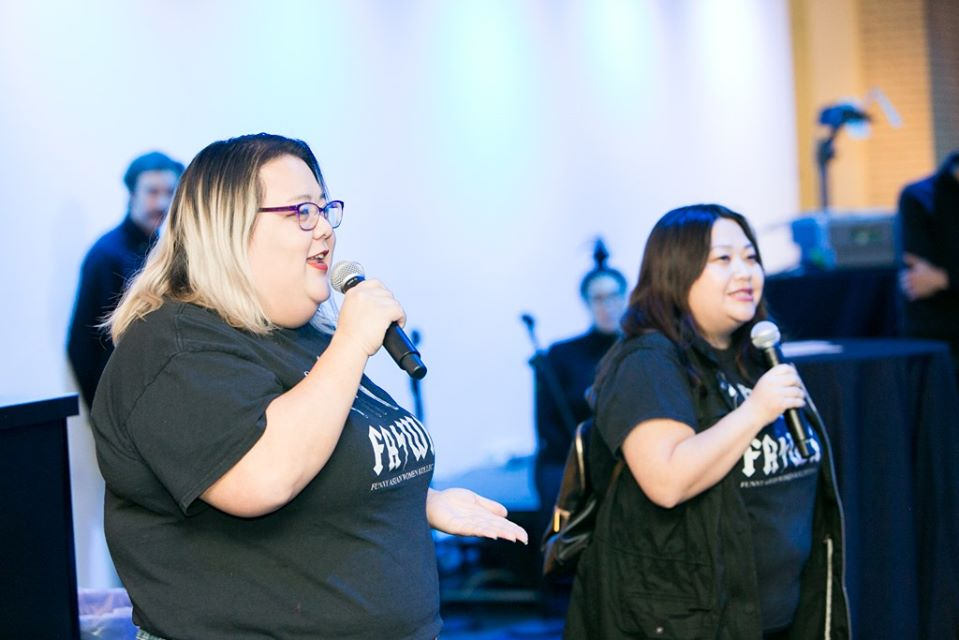 A picture of two members of Funny Asian Women Collective speaking on microphones