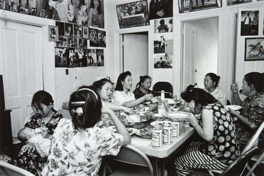 "A black-and-white photograph by Wing Young Huie titled ""Hmong Celebration, Frogtown"" shows eight Hmong women eating at a table."