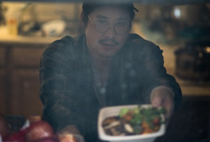 his is a picture of Kenji holding out a plate of food. The picture is blurry because it is taken through a window with a screen.""