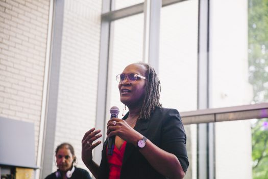 Council member Andrea Jenkins speaking into a microphone. She is wearing glasses and a black blazer with a red top. A DJ is in the background of the photo.