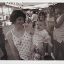 A woman holding a baby in the center of a crowd of people near a corn dog stand